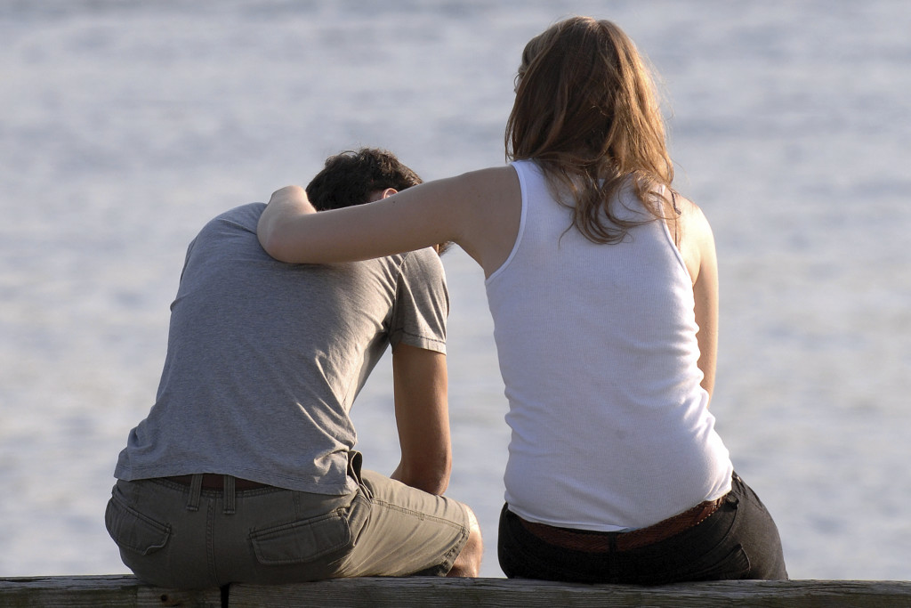 concerned-woman-comforts-frustrated-man-at-a-beach-000002302407_Medium